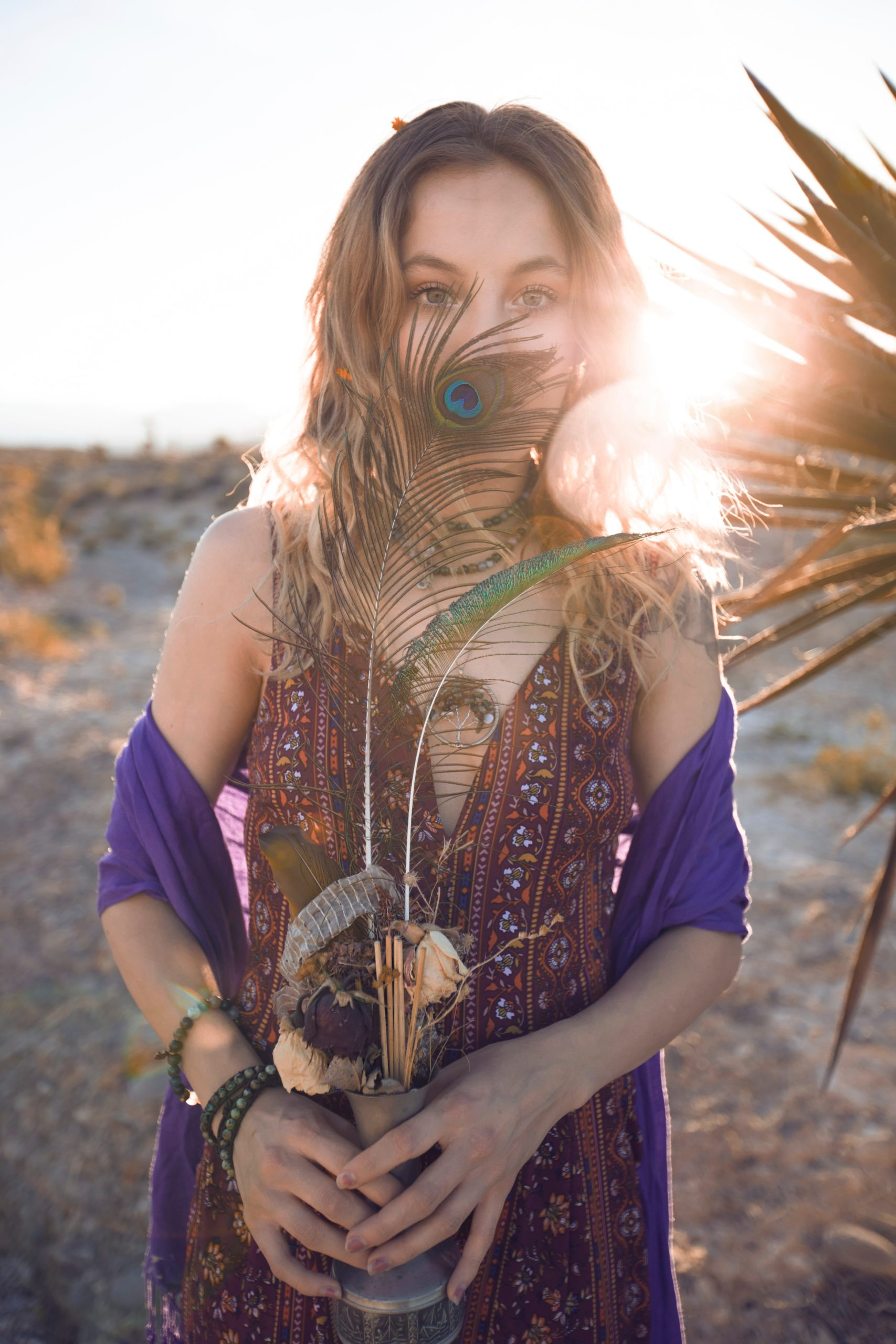 girl wearing boho outfit holding a flower