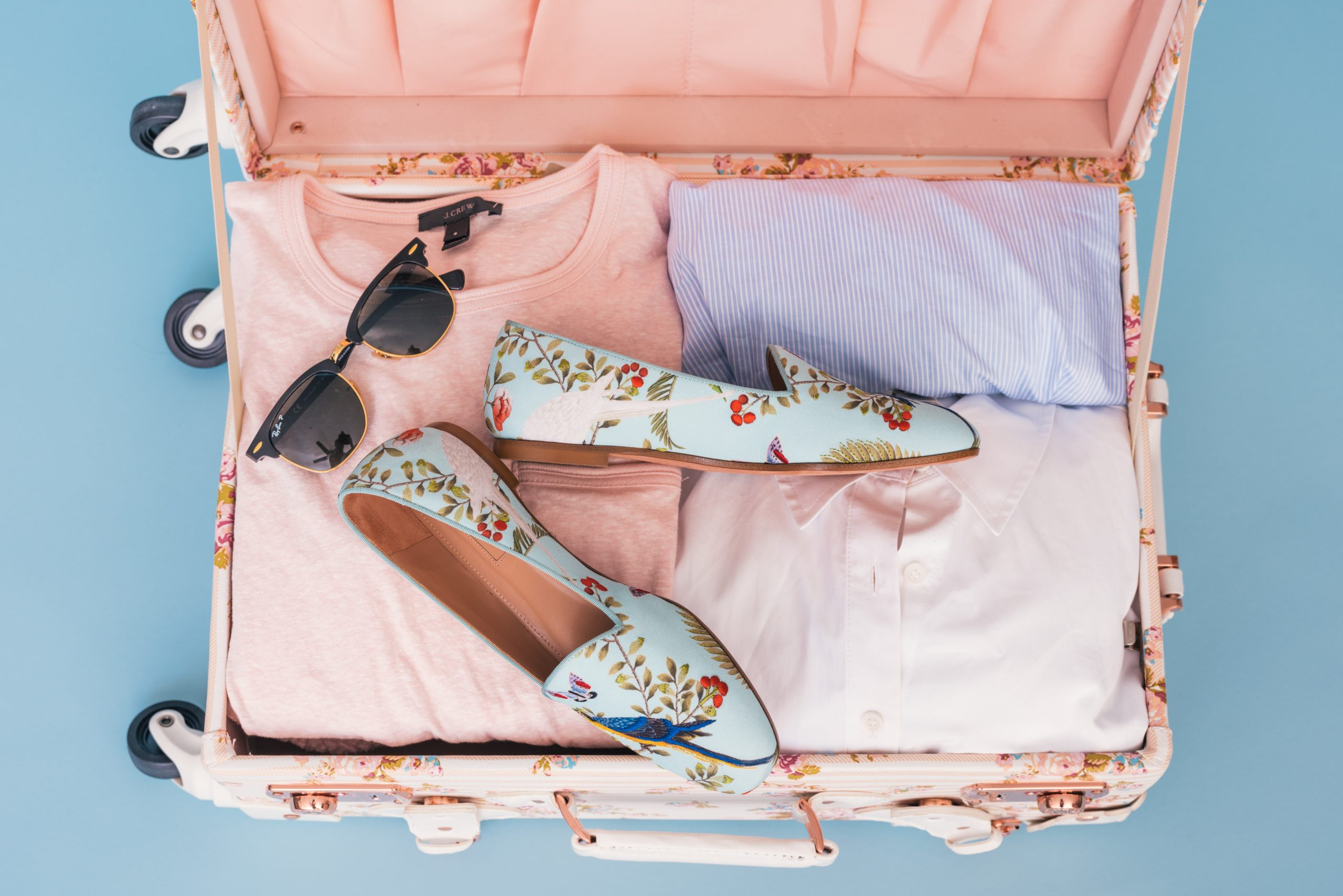 Pink suitcase packed neatly with essential travel items like sunglasses, shoes, and shirts.